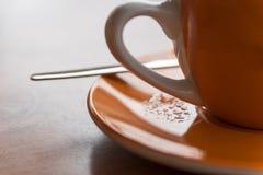 Pieza de una taza anaranjada del café o de té con la manija y el platillo Fotografía de archivo