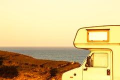 Pieza del campista en la costa en la puesta del sol Foto de archivo