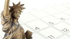 Pieza del primer de la estatua de la libertad de oro con el 4 de julio en la página del calendario aislada en el fondo blanco Imagenes de archivo