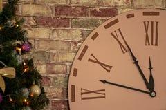 Pieza del reloj grande del reloj en la pared cerca del árbol de navidad Las flechas indican la época del acercamiento del Año Nue foto de archivo