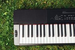 Pieza del teclado de piano eléctrico, fondo de la hierba verde Foto de archivo libre de regalías