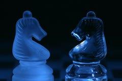 Piezas de ajedrez de cristal en luz azul Imágenes de archivo libres de regalías