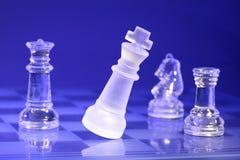 Piezas de ajedrez de cristal en luz azul Imagen de archivo