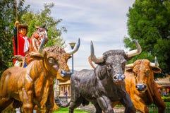 PIFO ECUADOR - NOVEMBER, 13, 2017: Utomhus- sikt av asfull skulptur av cowboyen som rider en häst med två enorma tjurar i a royaltyfria foton