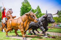 PIFO ECUADOR - NOVEMBER, 13, 2017: Utomhus- sikt av asfull skulptur av cowboyen som rider en häst med två enorma tjurar i a royaltyfri fotografi