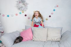 Pig as symbol of luck and Chinese 2019 new year calendar. Cute funny girl is surprised about A baby mini-pig on sofa stock photography