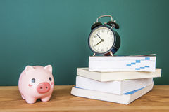Pig bank and a clock on a green background Stock Photo