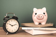 Pig bank and a clock on a green background Royalty Free Stock Image