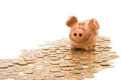 Pig bank seat on a heap of coins Royalty Free Stock Photo