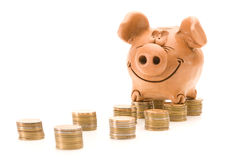 Pig bank seat on a stack of coins. Isolated over white background royalty free stock photos