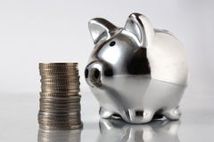 Pig bank and stack of coins Stock Images