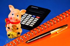 Pig calculating animal in a cheerful mood, able to anticipate events, a symbol of well-being. Notepad for important notes, a pen,. A calculator business royalty free stock images