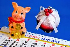Pig-Symbol of the year holiday calendar decoration toy elegant ball with bow. Pig calculating animal is always in a violent and cheerful mood, sincerely rejoices stock images