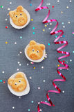 Pig Cookies on the Table with Sequence and Foil. Delicious Cute Pig Cookies on White Liners, Placed on the Table with Gray Textured Cloth with Colored Sequence Royalty Free Stock Photos