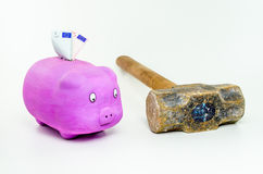 Pig with euro banknotes looking sledgehammer Stock Photos