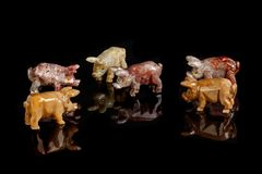 Pig figurines made of onyx, jasper, glass, gold on a black background royalty free stock image