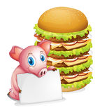 A pig holding an empty paper beside a pile of burgers Stock Photo