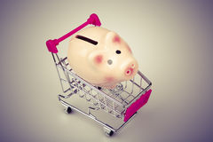 Pig money box in shopping cart on white background Royalty Free Stock Photos