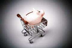 Pig money box in shopping cart on white background Royalty Free Stock Image