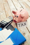 Pig moneybox and calculating equipment on wood background Stock Photo