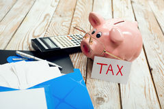 Pig moneybox and calculating equipment on wood background Royalty Free Stock Photos