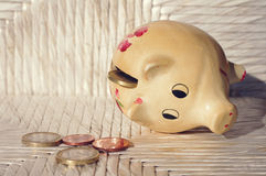 Pig moneybox with Euro coins on white wooden background. Royalty Free Stock Photography