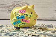 Pig moneybox and money. Saving money concept. Gathered pile of dollars and yellow pig Stock Image