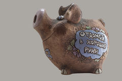 Pig moneybox, side view. Inscription on moneybox sides (in Russian): On the right side: I will give myself to the good owner On the left side: For modest Royalty Free Stock Images