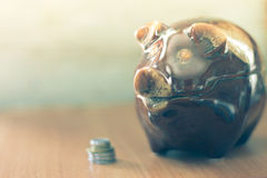 Pig piggy bank with coins on a wooden background Royalty Free Stock Photography