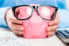 Pig stuffed with money in the hands of an economical woman close. Up with glasses Royalty Free Stock Photo
