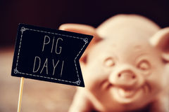Pig and text pig day. A black flag-shaped signboard with the text pig day and a pig in the background Royalty Free Stock Photography