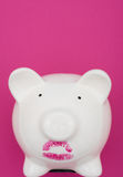 Pig Wearing Lipstick is Still a Pig. Pink piggy bank wearing red lipstick on pink background, pig wearing lipstick is still a pig Royalty Free Stock Photography
