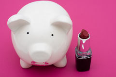 Pig Wearing Lipstick is Still a Pig. Pink piggy bank wearing red lipstick on pink background, pig wearing lipstick is still a pig Royalty Free Stock Image