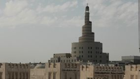 Souq Waqif mosque. Pigeon flying in the middle of Souq Waqif in front of mosque and minaret in Doha center, Qatar. Middle East, Arabian Peninsula. Sunny blue sky stock video footage