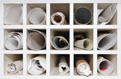 Pigeon Hole Storage. White pigeon hole storage cabinet filled with rolls of paper - maps, draftsman's drawings, architect's plans and other office documents Royalty Free Stock Images