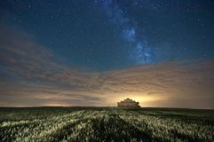 Pigeon house on wheat field at night under milky way starry sky with yellow clouds painted by light pollution