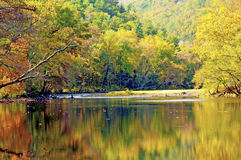 Pigeon River reflecting the colors of fall leaves. Royalty Free Stock Photo