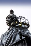 Pigeon sitting on Copernicus head. Nicolaus Copernicus Monument in the home town of astronomer Nicolaus Copernicus - Torun, Poland royalty free stock image