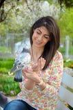 Pigeons de alimentation de belle jeune femme dans un jardin de ressort Image libre de droits