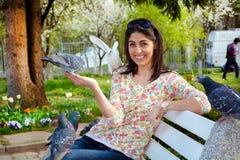 Pigeons de alimentation de belle jeune femme dans un jardin de ressort Image stock
