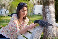 Pigeons de alimentation de belle jeune femme dans un jardin de ressort Photo libre de droits
