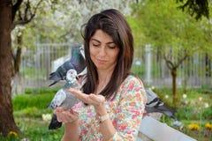 Pigeons de alimentation de belle jeune femme dans un jardin de ressort Photographie stock libre de droits