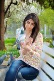 Pigeons de alimentation de belle jeune femme dans un jardin de ressort Photo stock