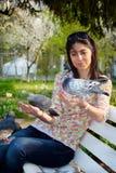 Pigeons de alimentation de belle jeune femme dans un jardin de ressort Photographie stock