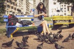 Pigeons de alimentation de jeune femme en parc Image stock