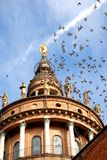 Pigeons in flight above the church Royalty Free Stock Photography