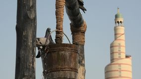 Old well Souq Waqif. Pigeons fly and drink around old well fountain, iconic landmark in the middle of Souq Waqif in Doha city center, Qatar. Middle East, Arabian stock footage