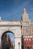 Pigeons flying above the Arch in Washington Square Park with Empire State Building in the background. – New York City Royalty Free Stock Images