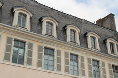 Pigeons are standing on the ridgepole of a building in Quimperle (France) Stock Photo
