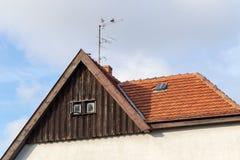Pigeons sur l'antenne sur le vieux toit en céramique rouge sous le ciel nuageux au coucher du soleil Photographie stock